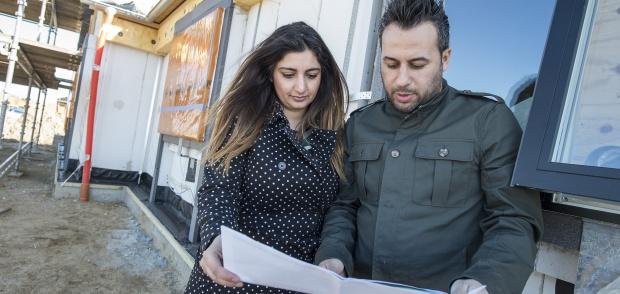 Foto af nybyggerpar foran deres kommende hus