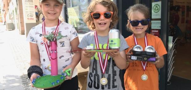 Børn der viser deres kreationer til skraldeworkshop i Det Grønne Rum